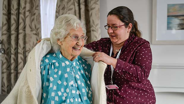 Home Carer putting on jacket for client