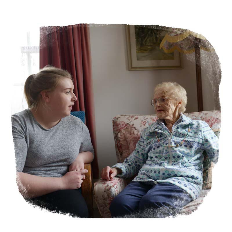 Dementia carer and client talking in a living room
