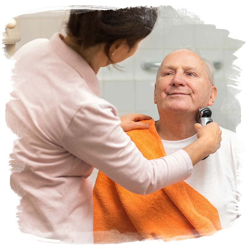 Home care assistant helping a client shave as part of his personal care plan.