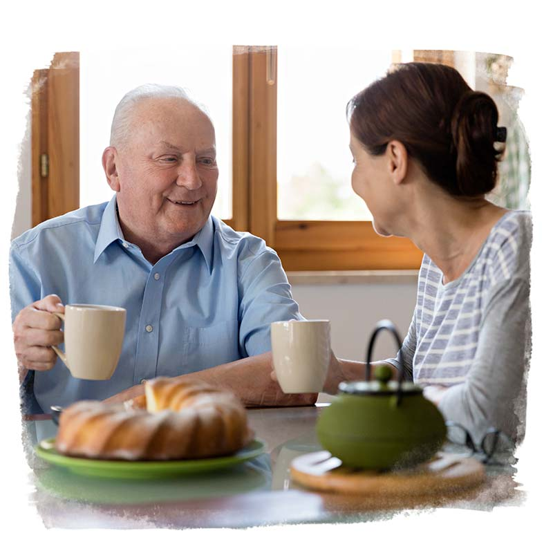 Home carer and client sitting together enjoying a pot of tea and cake.