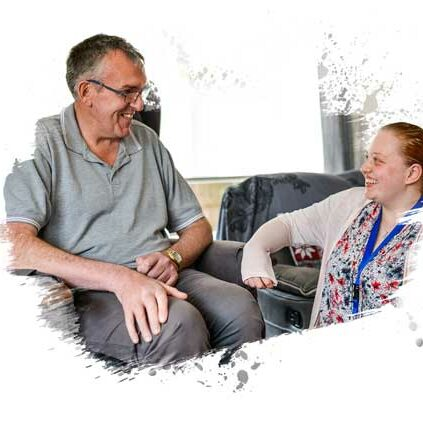 Live In Care Assistant kneeling and chatting with a seated client in her care